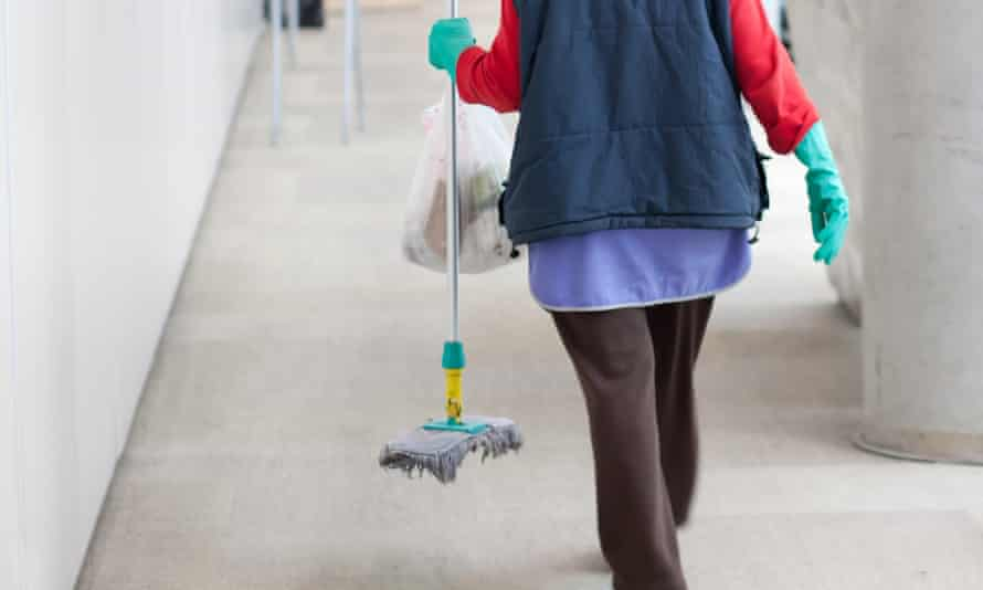 Person wearing rubber gloves holding a mop and rubbish bag seen from the back