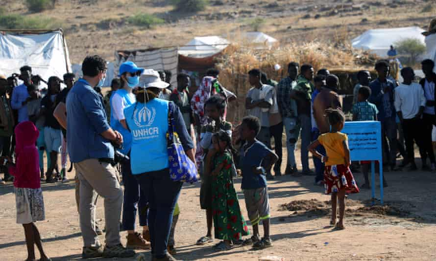 UNHCR personnel monitor food distribution at Um Rakuba refugee camp in Sudan, where Ethiopians fleeing the conflict in Tigray have taken shelter