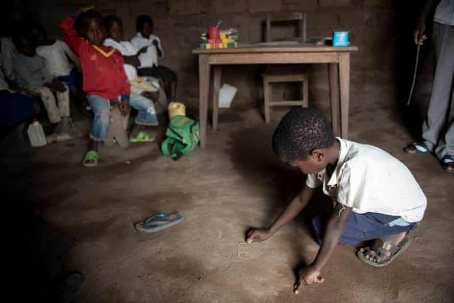 The floor is used as a writing pad by a child at Moma primary school in Nyunzu village, in eastern Congo's Katanga province