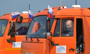 Putin sits in a dump truck before driving it on the newly opened bridge.