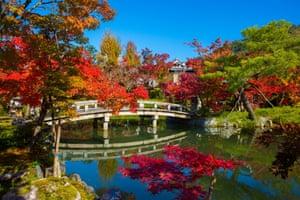 Kyoto, Japan. Jewel-toned autumn leaves surround the Bridge over Hojo pond, near Eikando Zenrin-Ji temple