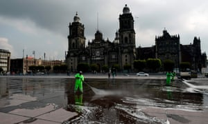 Workers disinfect and clean the Zocalo square in Mexico City on 29 June, 2020 during the Covid-19 pandemic.