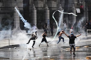 A protester throws a tear gas canister during a protest