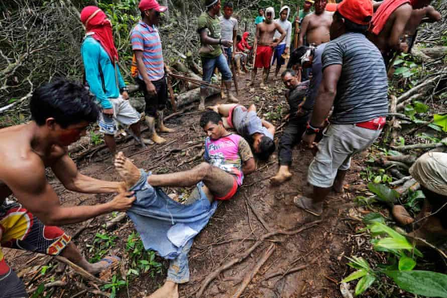 Ka'apor Indian warriors tie loggers during a jungle expedition in the Alto Turiaçu iregion