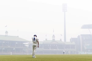Liam Hatcher of the Blues stands in the outfield amid the smoke haze from bushfires during day three of the Sheffield Shield cricket match between New South Wales and Queensland at the SCG on 10 December