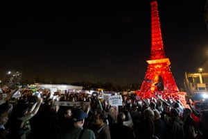 People from various NGOs gather near a mini replica Eiffel Tower