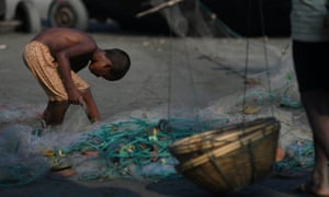 A Rohingya refugee boy scours a fishing net for leftovers