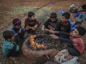 Children warm their hands around a fire at a refugee camp in Idlib, Syria