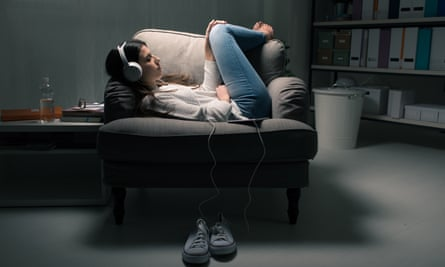Young woman curled up on a chair listening with headphones.