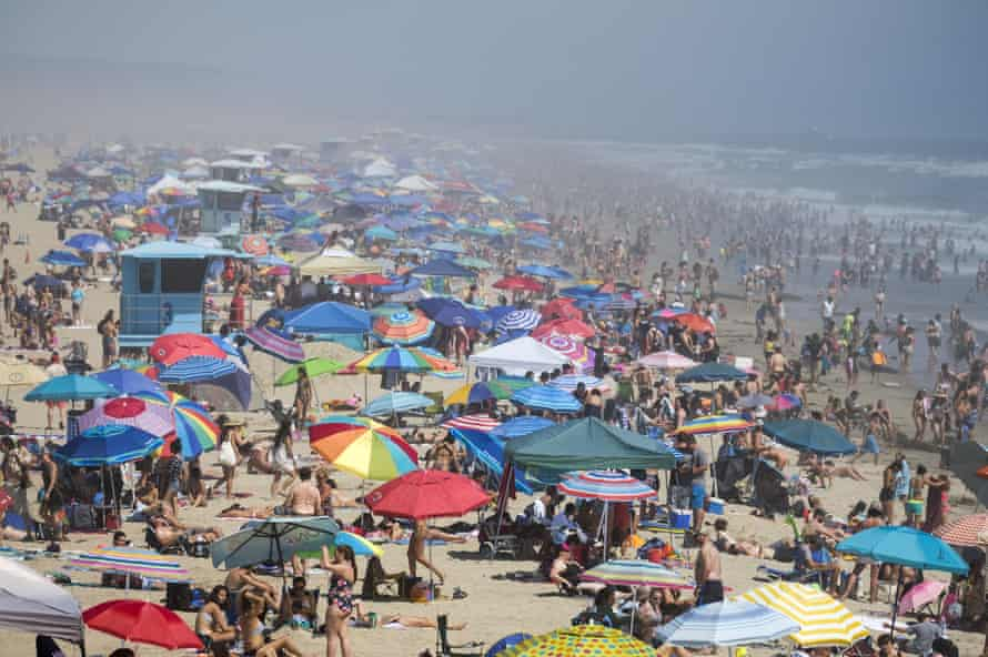 People cool off in the water on Huntington Beach, during record heat in California