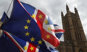 Anti Brexit protesters hold onto their flags and placards as they demonstrate outside the Houses of Parliament in London