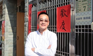 Tung Sen-po standing by a gate with Chinese signs hanging on it in the street