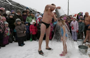 Visitors watch as Grigory Broverman pours a bucket of cold water over his six-year-old daughter Liza