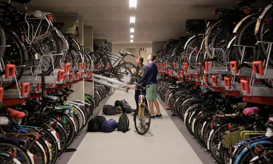 Two cyclists parks their bikes in the parking garage in Utrecht