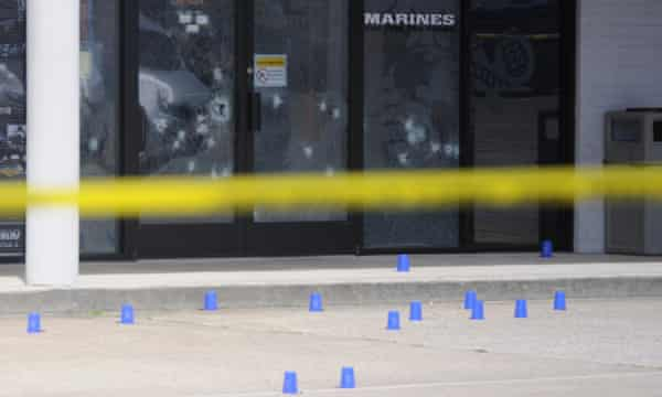 The windows of the Armed Forces Recruitment Center have several bullet holes from a shooting as the area is cordoned off with blue shell casing markers in the parking lot on Thursday in Chattanooga, Tennessee.