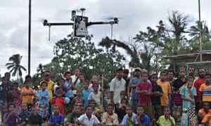 Group of people with a drone flying in the foreground