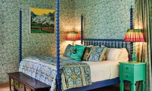 A bedroom with blue patterned bedding on a four-poster and green wallpaper at Suite 67 at Belmond La Residencia