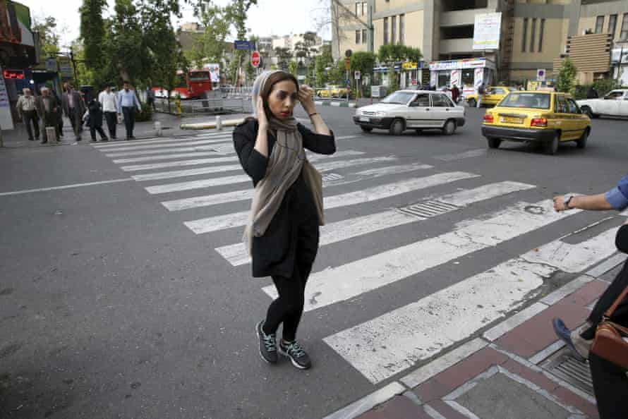 An Iranian woman adjusts her head scarf while crossing a street in downtown Tehran, Iran.