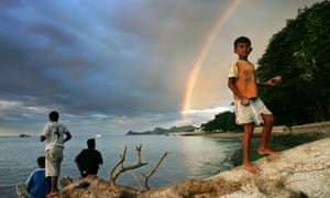 An East Timorese youth walks as a streak of rainbow is seen in the background in Dili, Timor-Leste's capital. The