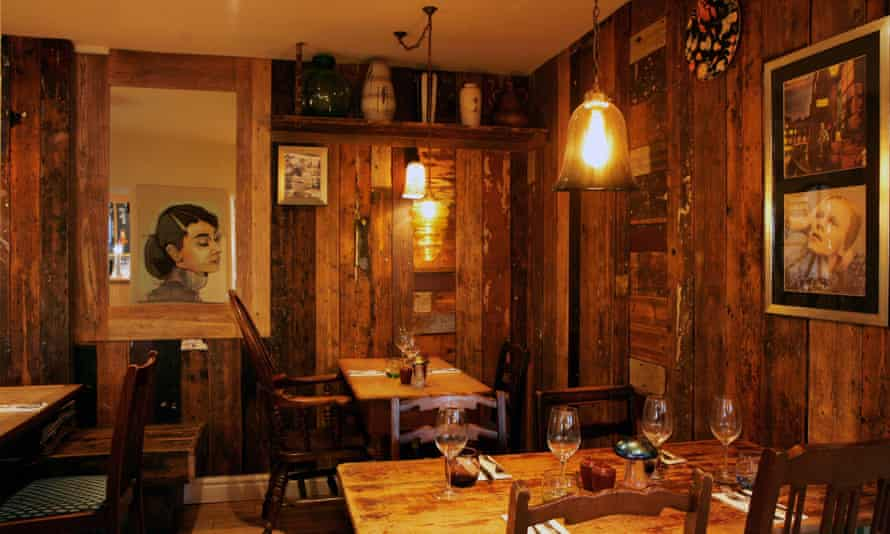 Interior of the Cartford Inn with wood panelled walls, wooden tables and chairs and pictures on the walls