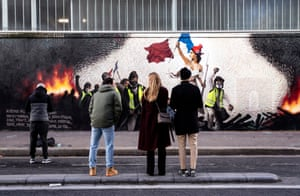 People look for clues in a mural in Paris, France