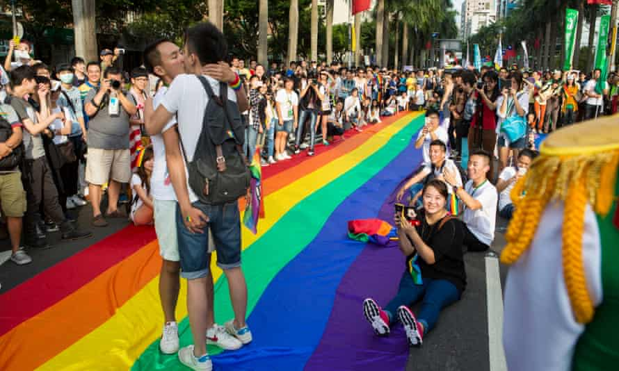 Two gay men kiss standing on the rainbow banner during the annual gay pride march through Taipei's city streets.