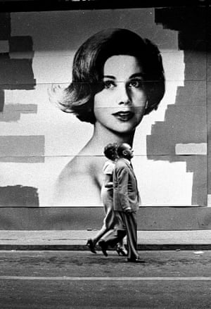 A couple pass a poster of a woman
