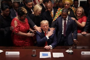 African American supporters lay their hands on US president Donald Trump as they pray for him at the conclusion of a news conference and meeting in the Cabinet Room at the White House. The president talked about the economic advances African Americans have made under his administration, about the government's response to the global coronavirus threat and how dishonest he thinks the news media can be to him.