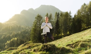 A woman practises yoga on an Alpine mountainside
