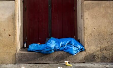 A homeless person asleep in a doorway.