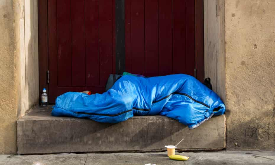 A homeless man sleeps in a doorway on Oxford Road, Manchester.