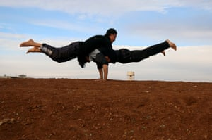 """Parkour coach Ibrahim al-Kadiri, 19, and Muhannad al-Kadiri (top), 18, demonstrate their parkour skills in the rebel-held city of Inkhil, west of Deraa, Syria, February 4, 2017. """"I love competing with my friends to achieve the highest jump,"""" Muhannad says."""
