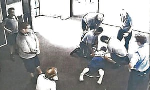 A boy, 17, is placed in handcuffs and ankle cuffs in Cleveland youth detention centre in Queensland. The state government is being urged to raise the age of criminal responsibility to 14.