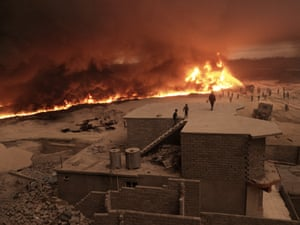 A family watches from their rooftop as firefighters struggle to extinguish walls of flames creeping closer to their home in Qayyarah in Iraq.