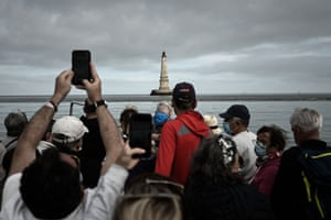 Visitors take photographs from a boat
