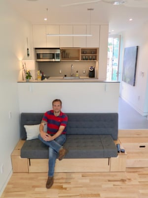 James Stinson inside a Kasita. The sofa is a pull-out bed, and the steps conceal storage.