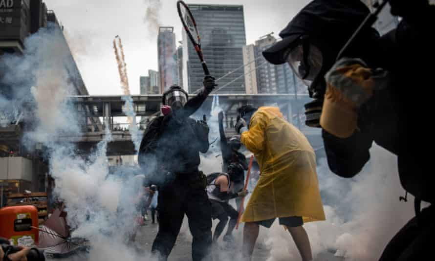 A protester uses a tennis racquet to hit back tear gas canisters during clashes with police after an anti-government rally in Hong Kong
