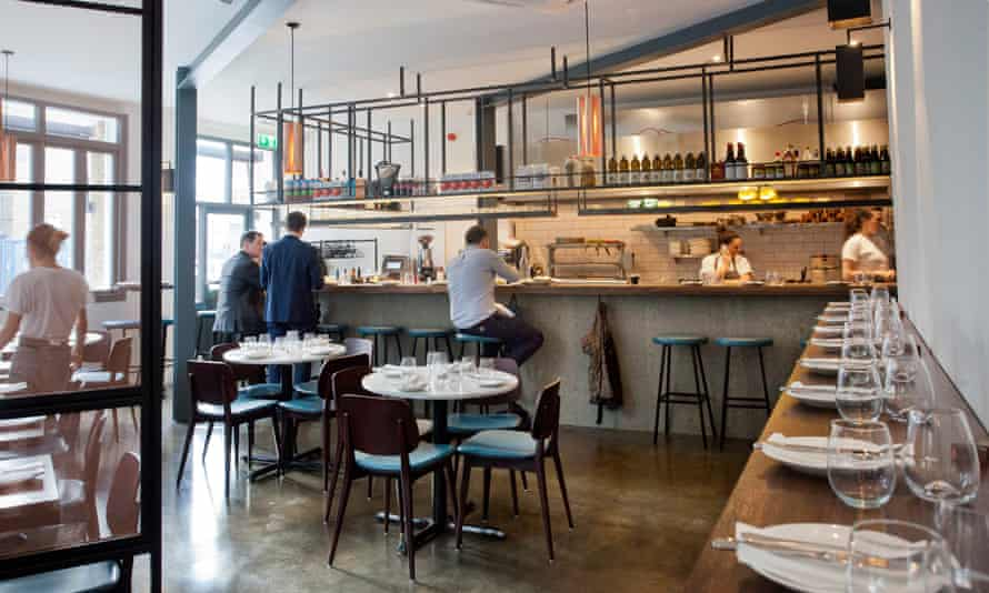 A counter with plates and glasses stretches to a serving counter, with stools in front, and chairs and tables around at Oklava