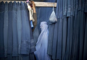 A fully covered Afghan woman in blue against a series of hanging blue burqas that appear like a blue curtain behind her