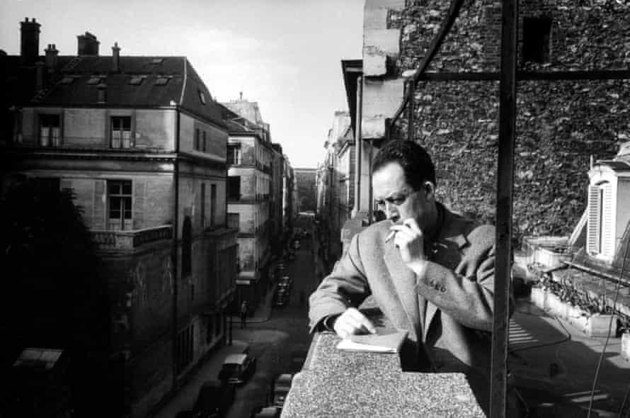 Albert Camus smoking cigarette on balcony outside his publishing firm office.