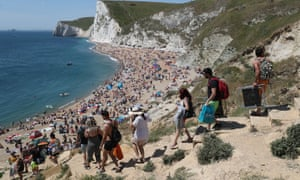 People make their way down to the beach at Durdle Door, near Lulworth