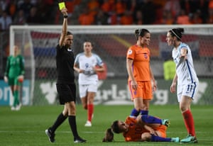 Jade Moore receives the yellow card from French referee Stephanie Frappart.