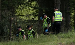 Police search woodland near junction 9 of the M9 motorway, where Yuill and Bell were discovered in their car on Wednesday.