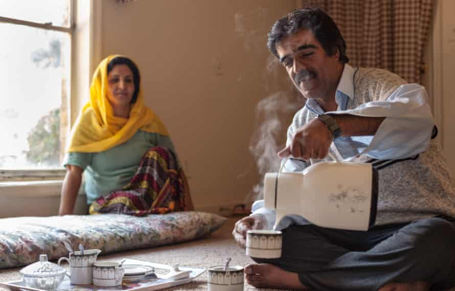 Hekmatullah, an Afghan refugee, pours chai as his wife Waheeda watches on. Hekmatullah worked as a journalist for 25 years before coming to America. He now works in a retail distribution center in Atlanta.