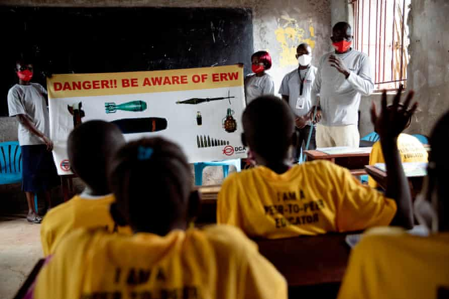 Children sing songs and mime actions they have been taught to protect them from landmines and other improvised explosive devices