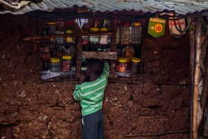 A boy buys sweets for a few coins from a stall in Kibera