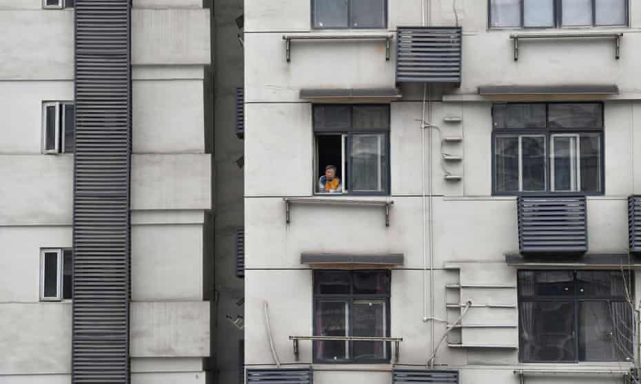 A man looks out of the window of a residential building in Wuhan, the centre of the original coronavirus outbreak