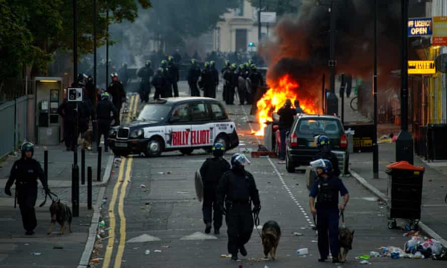 Riot police on the scene after cars were set alight by rioters in Hackney, north London, on 8 August 2011