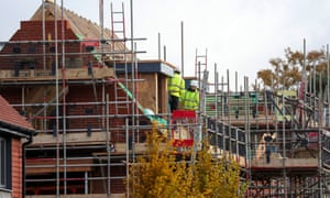 Construction workers on scaffolding around new houses being built