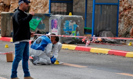 Forensics experts inspect the site where two Israelis were killed at a West Bank bus stop